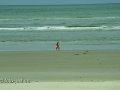 Frau mit Kindern spazieren am Strand